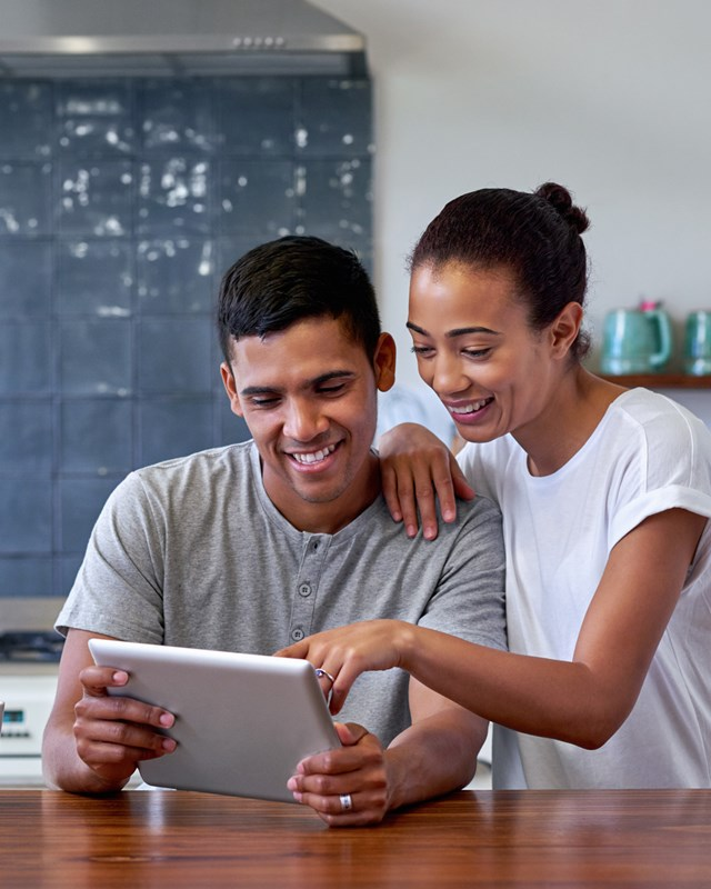 young happy couple on a tablet in the kitchen