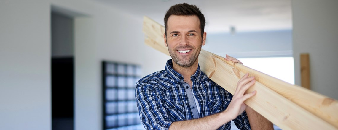 friendly home improvement professional carrying wood at job site